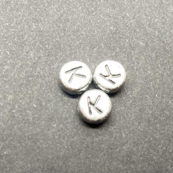 Műanyag ezüst színű kör k betűgyöngy (7mm)